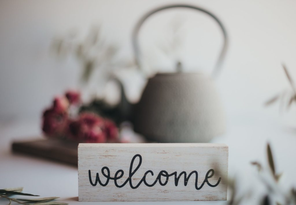 Welcome written on piece of wood with tea pot and flowers in background